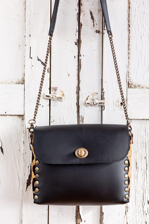 bolso negro con detalles dorados , bandolera de piel animal print con cadenas